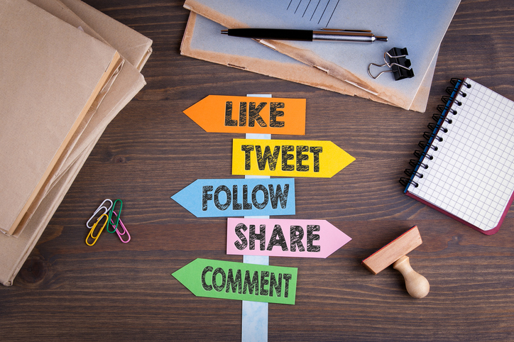 social media concept (like, tweet, follow, share, comment). Paper signpost on a wooden desk